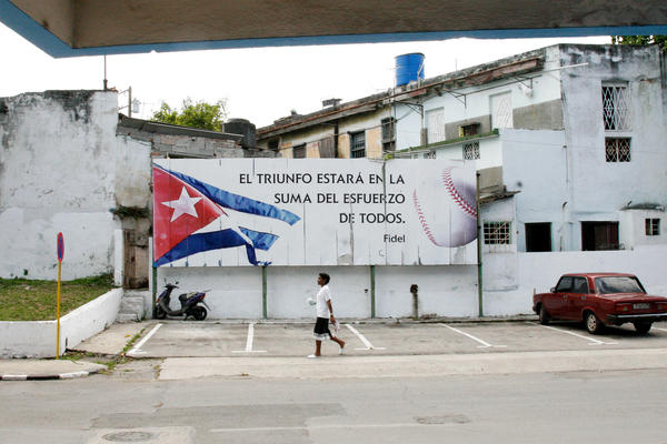 "A sign in front of the stadium features a quote from Fidel Castro: ""Triumph is found in the sum of all our efforts."""