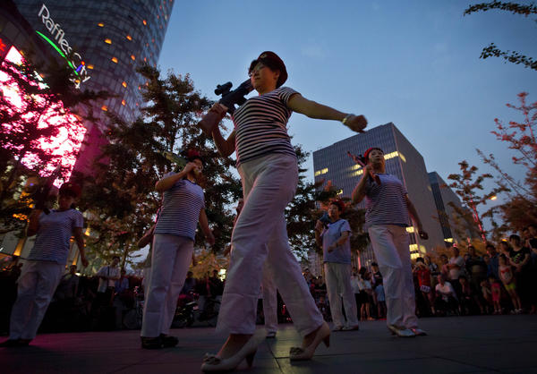 Chinese women holding toy guns dance to a revolutionary song during their daily exercises at a square outside a shopping mall in Beijing. The Chinese government is beginning to regulate public square-dancing, after the practice drew complaints about noise.