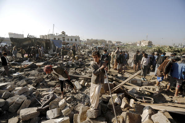 People examine the rubble following an air strike near the airport in Yemen's capital Sanaa on Thursday. Saudi Arabia said it carried out bombing raids in neighboring Yemen as Houthi rebels, allied with Iran, continued their offensive in the country. Yemen's president fled the country Wednesday and was reported to be in Saudi Arabia on Thursday.