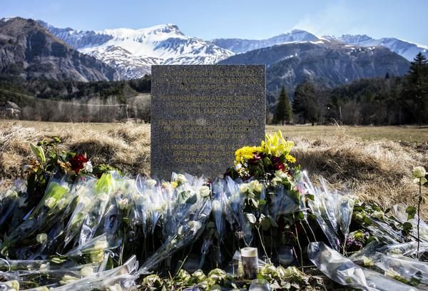A stone memorial, surrounded by flowers, has been placed near the site in the French Alps where a Germanwings passenger jet crashed on Tuesday (March 24, 2015). Investigators believe the jet's co-pilot brought it down deliberately.