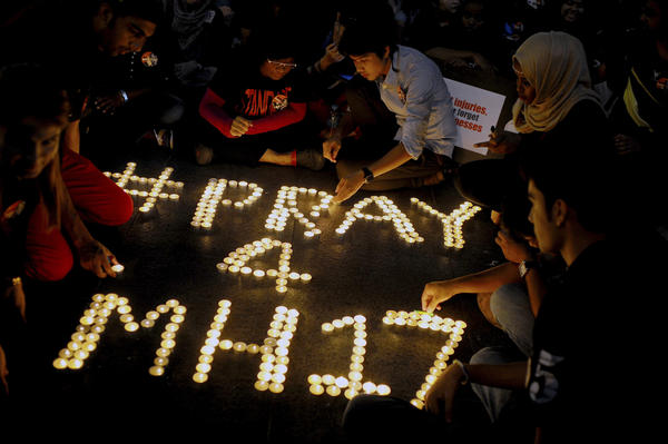 People arrange candles to offer prayers for the victims of the Malaysia Airlines Flight 17, at a shopping mall in Petaling Jaya, Malaysia. All sides in the conflict in Ukraine — Kiev, the separatists, and Moscow — have denied any involvement in the downing of MH17.