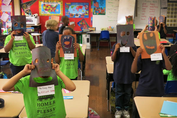 Second-graders in Chantell Nabonne's class hold up their masks, part of a class project on New Orleans's culture and art.
