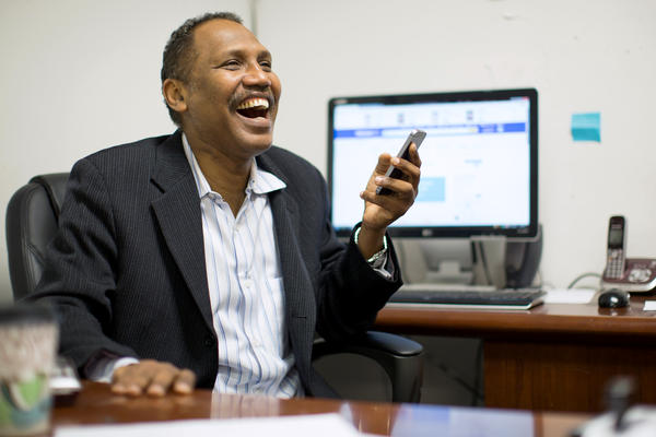 Omar Shekhey has a laugh while fielding questions and phone calls at the Somali American Community Center in Clarkston, Ga. Shekhey, who runs the nonprofit group, has been helping Clarkston's refugee community for several years though the center and an after-school program.