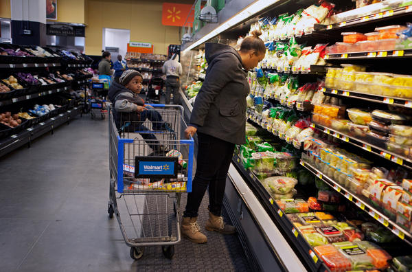 A customer shops for groceries with her son at the Wal-Mart on H Street in Washington, D.C.