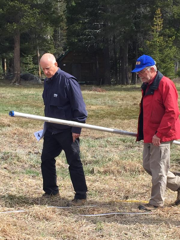 California Governor Jerry Brown with Frank Gehrke, state chief of snow surveys, in a meadow that usually has four to five feet of snow. Brown announced statewide mandatory water reductions at the site.