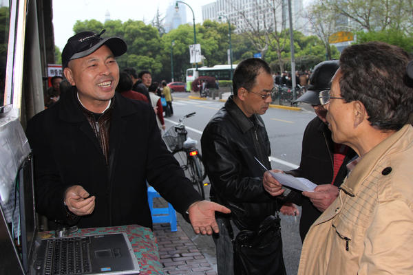 Shen Yuxi pitches stocks from a Shanghai street corner. He tells his audience to always buy stocks from the Communist Party leader's home province because, he says, investment naturally flows in that direction in China.