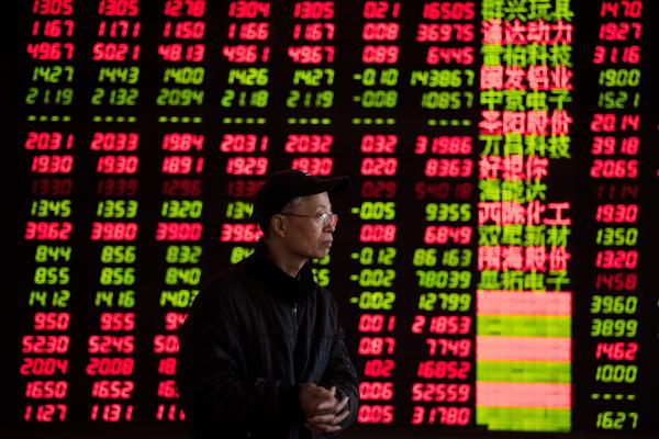 An investor looks at stock information at the trading hall of a securities firm in Shanghai in January.