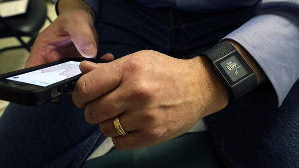 Patient Gary Wilhelm looks at his medical data on a smartphone that is synchronized to a new Fitbit Surge on his wrist.
