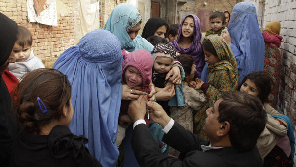 A health worker injects a vaccine to prevent polio and measles in Lahore, Pakistan.