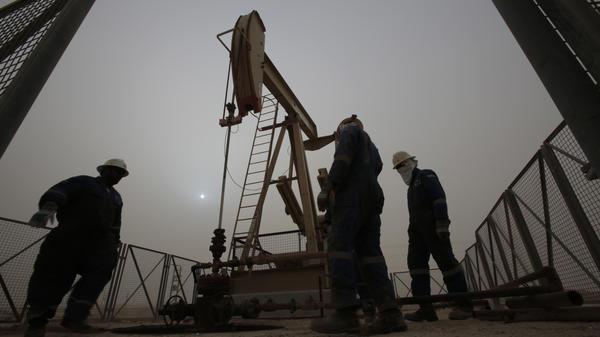 Men work on an oil pump during a sandstorm in the desert oil fields of Sakhir, Bahrain, in January.