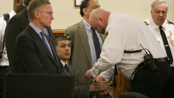 A court officer places handcuffs on the wrists of former NFL player Aaron Hernandez after he was found guilty of first-degree murder Wednesday at the Bristol County Superior Court in Fall River, Mass.