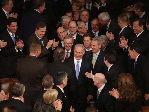 Israeli Prime Minister Benjamin Netanyahu is greeted by members of Congress before speaking to a joint meeting in the House chamber.