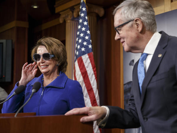 House Minority Leader Nancy Pelosi starts a news conference by donning dark glasses, a teasingly sympathetic gesture to Reid.