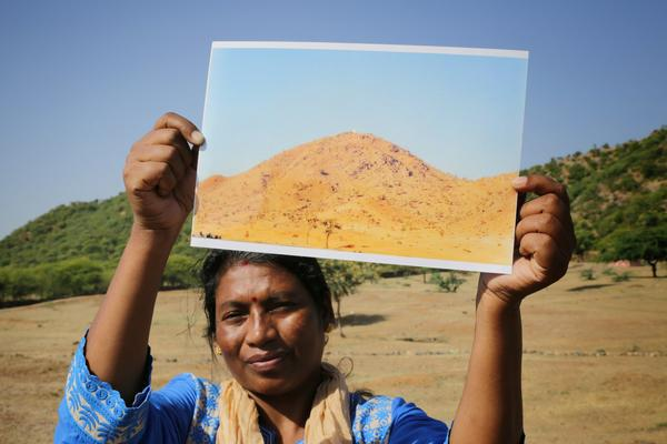 An Indian woman in the village of Rajasthan holds up a photo of what the hillside behind her once looked like. The organization Foundation for Ecological Security improves public land so it can be a better place for growing food.