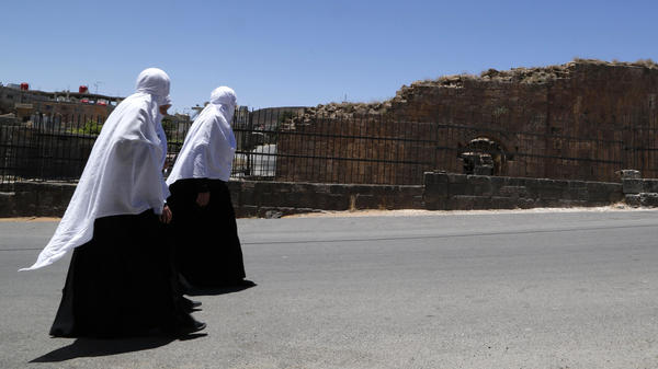 Druze women walk beside Roman ruins in Shahba, in southwest Syria, last June. The Druze are one of several minority communities that have generally tried to avoid direct involvement in Syria's civil war.