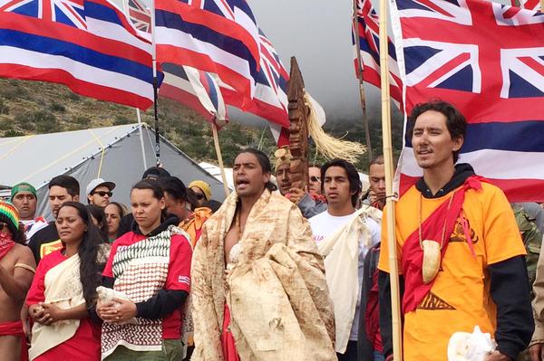 Telescope opponents Lanakila Manguil (center) and Kahookahi Kanuha (right) lead a <em>pule,</em> or prayer, atop Mauna Kea.