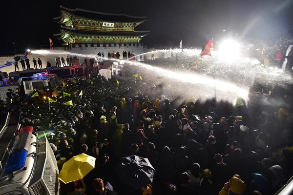 Riot police spray South Korean protestors with water cannons in front of the main gate to the Gyeongbok Palace, during a rally to commemorate the first anniversary of the Sewol ferry disaster in Seoul on Saturday.