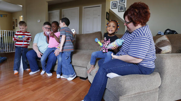 Rowse (left) and DeBoer at home with their four children in Hazel Park, Mich. Because Michigan will not allow a same-sex couple to adopt, but will let a single person adopt, Jayne has adopted two of the children and April the other two.