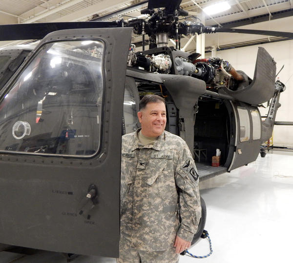 Col. David Caporicci, deputy commander of the 66th Theater Aviation Command, stands beside a UH-60 Blackhawk helicopter. After 28 years, budget cuts may threaten his job.