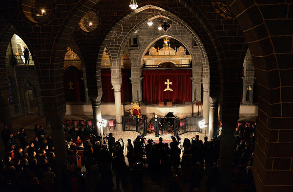 People attend a concert by Armenian pianist Raffi Bedrosya at St. Grigaros Church in Diyarbakir on Thursday. The event marked the 100th anniversary of the massacre of an estimated 1.5 million Armenians by Ottoman forces.