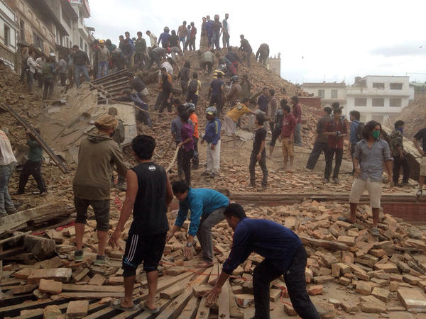 Volunteers help with rescue work at the site of a building that collapsed after an earthquake in Kathmandu, Nepal, on Saturday. The temblor is the worst in Nepal in 80 years.