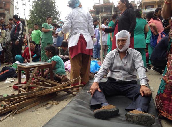 Injured people receive treatment outside the Medicare Hospital in Kathmandu, Nepal, on Saturday.
