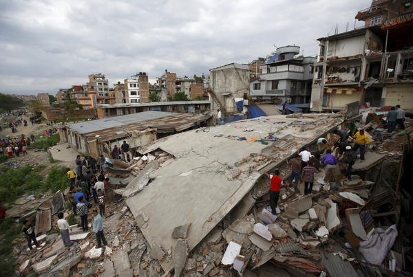 People gather near a collapsed house after a major earthquake in Kathmandu, Nepal.