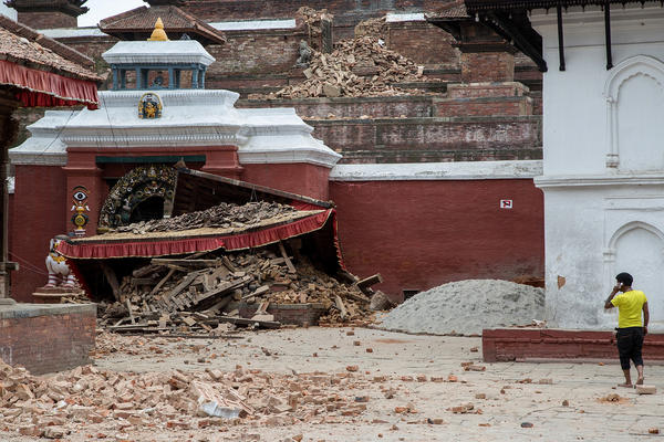 A young man speaks on the phone in front of a collapsed temple in the city center following an earthquake on April 25, 2015 in Kathmandu, Nepal. A strong magnitude-7.8 earthquake shook Nepal's capital and the densely populated Kathmandu Valley before noon Saturday, causing extensive damage.