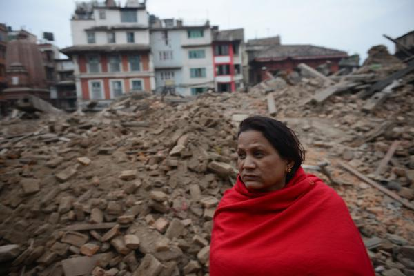 A Nepalese resident sits near buildings severely damaged by an earthquake on Kathmandu on Sunday.