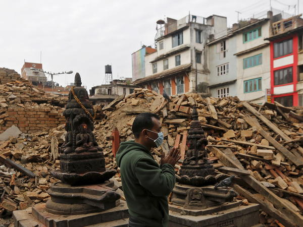 A man prays next to rubble of a temple destroyed in Saturday's earthquake in Kathmandu.