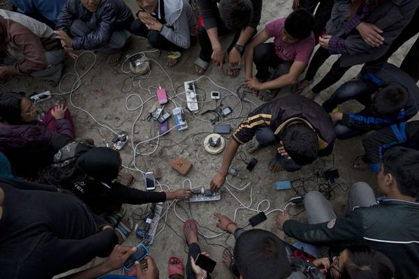 Nepalese villagers charge their cell phones in an open area in Kathmandu, Nepal, Monday, April 27, 2015. (Bernat Armangue/AP)