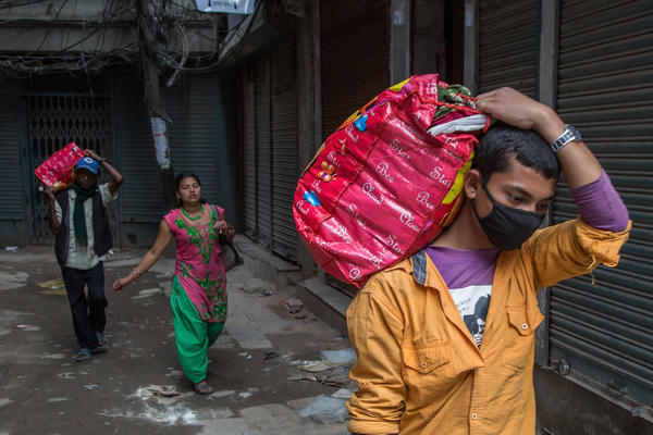 Residents carry belongings out of their home to use in a temporary shelter in Kathmandu.