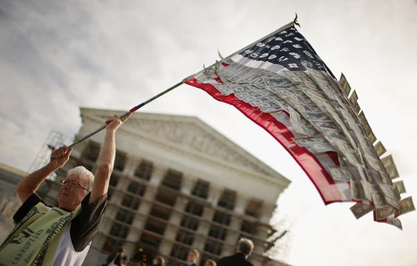 David Barrows, of Washington, D.C., waves a flag with corporate logos and fake money during a rally against money in politics outside the Supreme Court in 2013.