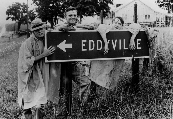 Dan Walker, center, behind a sign pointing toward Eddyville.