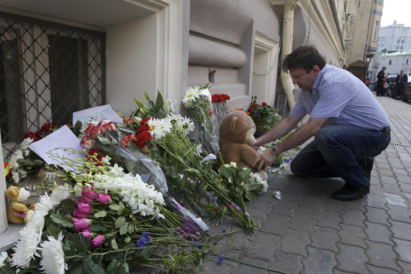 A man lays a stuffed bear among flowers outside the Dutch Embassy in Moscow. More than half of Flight MH17's passengers were from the Netherlands.