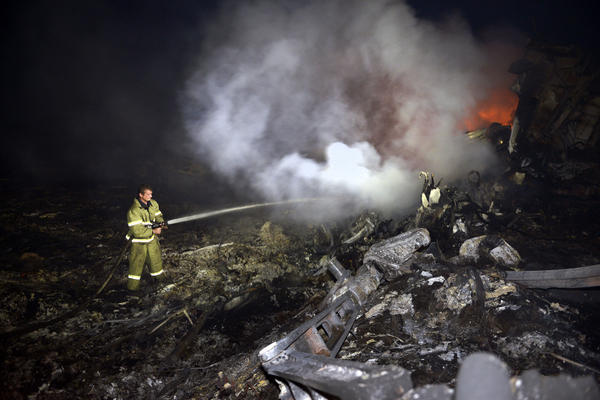 A firefighter douses the smoldering wreckage of Flight MH17 on Thursday. Kiev officials accuse pro-Russian separatists of firing a missile at the jet, which crashed in territory held by rebel insurgents. The separatists, Ukraine's military and Russia have all denied any involvement.