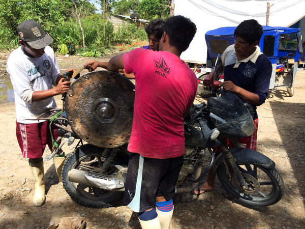 Men strap replacement parts for mining equipment onto the back of a motorcycle. The only way to reach many of the gold mines is with dirt bikes on narrow trails through the jungle.