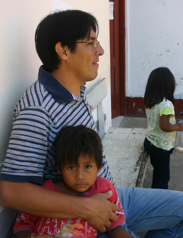 Dr. Fernando Medieta holds the brother of a baby being treated for severe anemia.