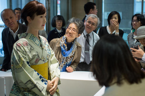 """Shoppers view and take photographs of humanoid robot """"Chihira"""" at the information reception desk of Mitsukoshi department store in Tokyo."""