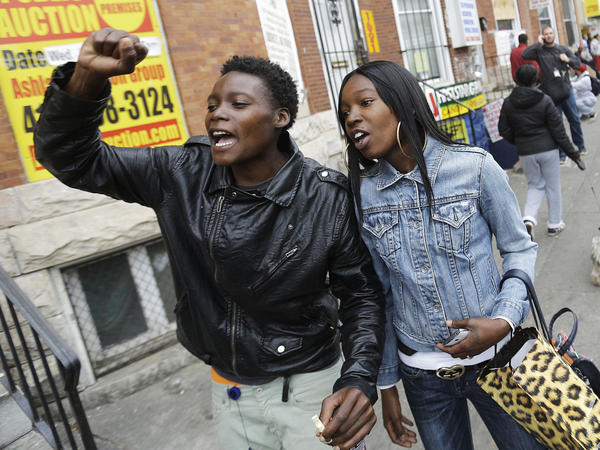 Charvae Day and Renay Battle react after the city's top prosecutor, Marilyn Mosby, announced criminal charges against all six officers suspended after Freddie Gray suffered a fatal spinal injury while in police custody.
