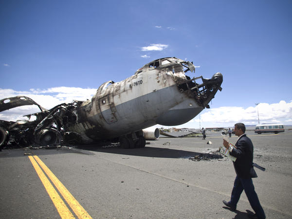 An airport official walks past a military aircraft destroyed by Saudi-led airstrikes, at the Sanaa International airport in Yemen on Tuesday. Destroyed runways prevent aid from being delivered.