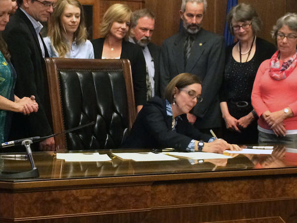 Oregon Governor Kate Brown signs a bill to require criminal background checks on private gun sales.