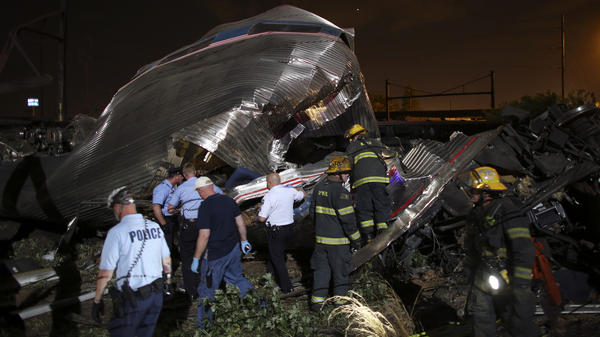 Emergency personnel search through the wreckage of an Amtrak train that derailed Tuesday night in Philadelphia, killing at least five people who were on board.