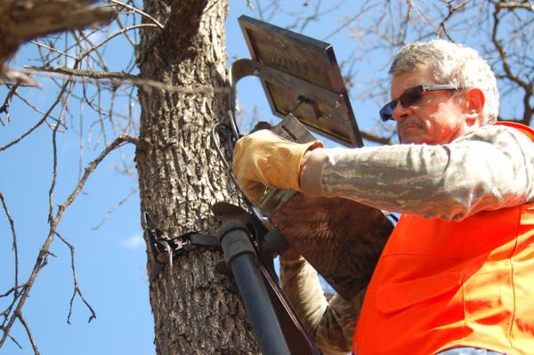 <p>John McGowan sets up a camera at Oak Creek Wildlife Area.</p>
