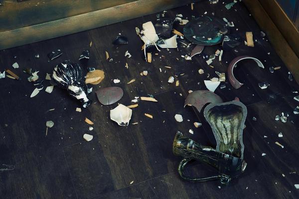 Shards of smashed Asian vases litter the floor of Waterston's <em>Filthy Lucre.</em>