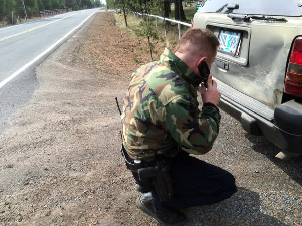 <p>James Hayes examines the damage on a car he suspects was involved in a hit-and-run. Budget cuts in local law enforcement has led to some Fish and Wildlife troopers handling more general law enforcement.</p>