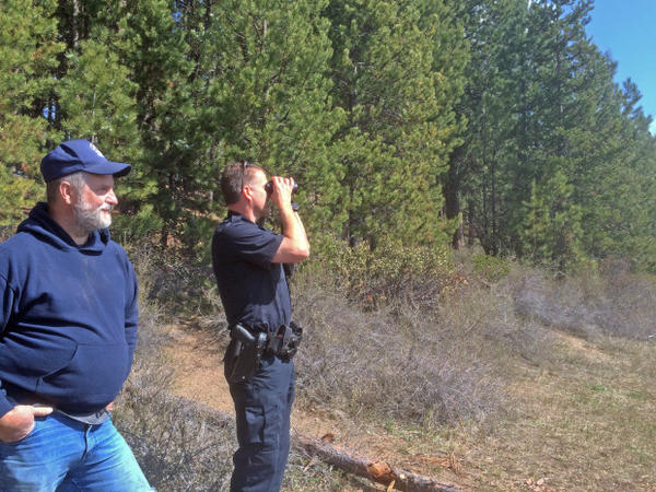<p>Darin Bean looks through binoculars at Twin Lakes while chatting with La Pine resident and fisherman Larry Archer. Bean cited Archer in the past for shooting a wildlife decoy.</p>