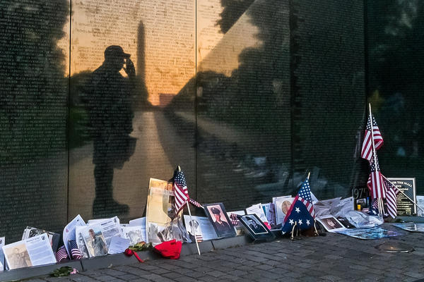 """Army veteran Bernie Klemanek, of Mineral, Va., stops to salute his fallen comrades on Memorial Day during an early morning visit Monday to """"The Wall"""" at the Vietnam War Memorial in Washington."""
