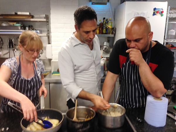 From left: Recipe developer Esme Robinson, chef-owner Yotam Ottolenghi and Nopi head chef Ramael Scully hover over the electric stovetop while preparing a dessert in the Ottolenghi test kitchen in London.