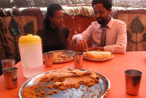 Customers enjoy a meal at Chef Chane's. He only serves one dish per day. Whatever the meal is, it's always served on top of a spongy sourdough flatbread called <em>injera </em>that doubles as a plate<em>.</em>
